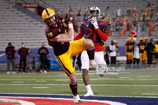 Wide receiver Ricky Pearsall of the Arizona State Sun Devils catches a 31-yard touchdown reception past defensive back of the Arizona Wildcats during...