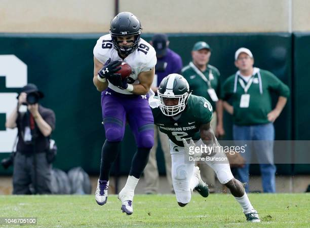 Wide receiver Riley Lees of the Northwestern Wildcats makes a catch in front of cornerback Justin Layne of the Michigan State Spartans during the...