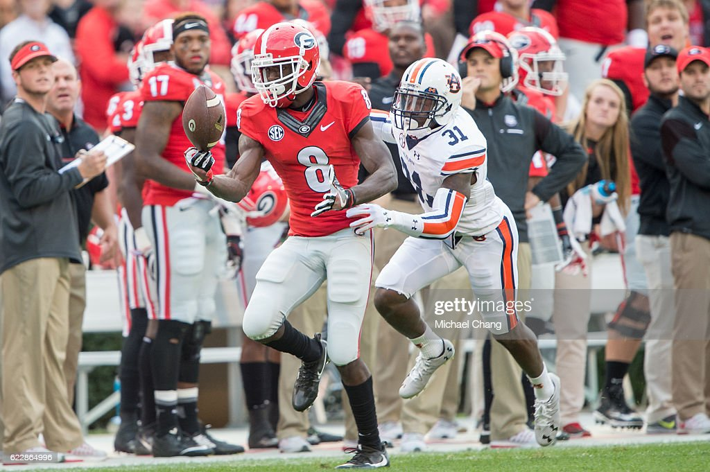 Wide receiver Riley Ridley #8 of the Georgia Bulldogs catches a pass in front of defensive back Javaris Davis #31 of the Auburn Tigers at Sanford Stadium on November 12, 2016 in Athens, Georgia.
