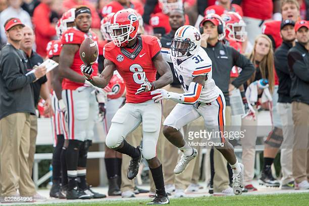 Wide receiver Riley Ridley of the Georgia Bulldogs catches a pass in front of defensive back Javaris Davis of the Auburn Tigers at Sanford Stadium on...