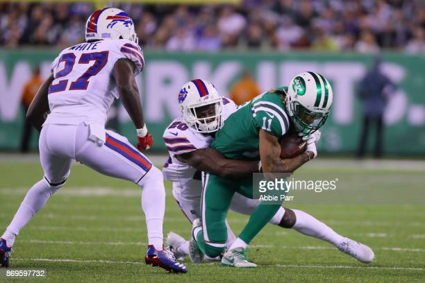 wide receiver Robby Anderson of the New York Jets is tackled by cornerback Shareece Wright of the Buffalo Bills as cornerback Tre'Davious White looks...