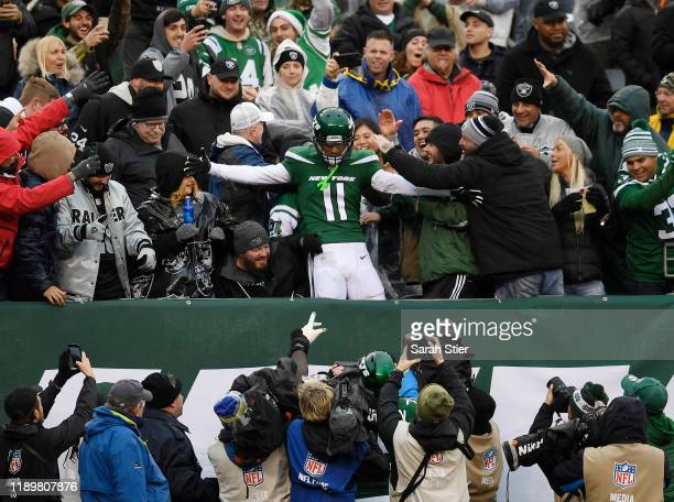 Wide receiver Robby Anderson of the New York Jets jumps into the stands after scoring a touchdown during the second half of the game against the...