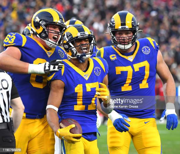 Wide receiver Robert Woods is congratulated by offensive guard Austin Corbett and offensive tackle Andrew Whitworth of the Los Angeles Rams after...