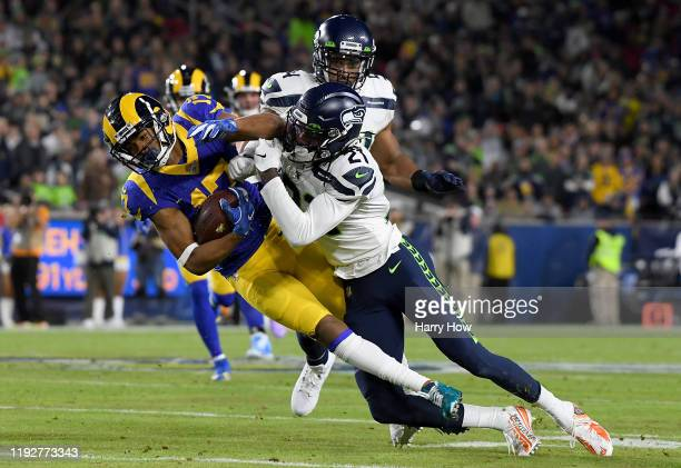 Wide receiver Robert Woods of the Los Angeles Rams is hit by at cornerback Tre Flowers of the Seattle Seahawks during the game at Los Angeles...
