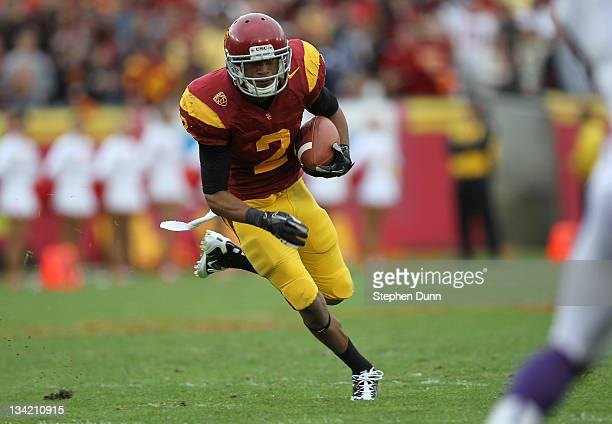 Wide receiver Robert Woods of the USC Trojans carries the ball against the Washington Huskies at the Los Angeles Memorial Coliseum on November 12,...