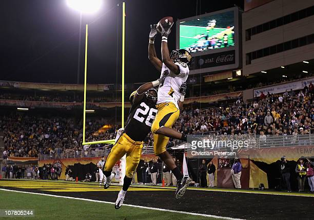 Wide receiver Rolandis Woodland of the Missouri Tigers is unable to catch a reception over Shaun Prater of the Iowa Hawkeyes during the Insight Bowl...