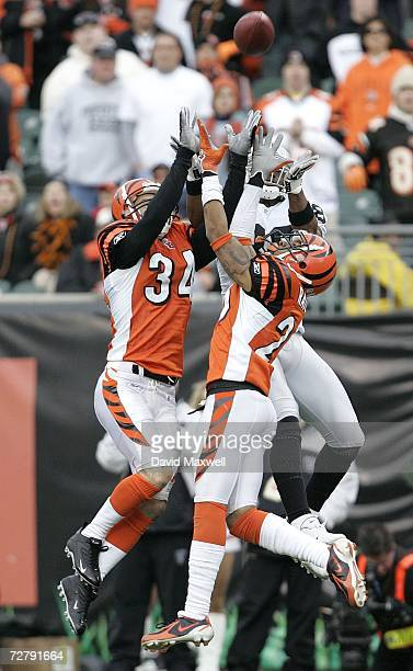 Wide receiver Ronald Curry of the Oakland Raiders goes up for a pass against Keiwan Ratliff and Kevin Kaesviharn of the Cincinnati Bengals on a...