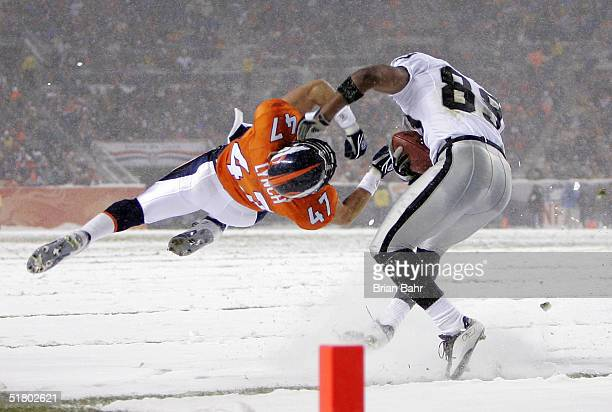 Wide receiver Ronald Curry of the Oakland Raiders makes a catch against John Lynch of the Denver Broncos on November 28 2004 at Invesco Field at Mile...
