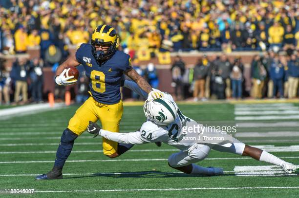 Wide Receiver Ronnie Bell of the Michigan Wolverines breaks a tackle of Tre Person of the Michigan State Spartans during the first half of a college...