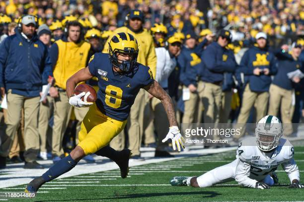 Wide Receiver Ronnie Bell of the Michigan Wolverines runs past a Michigan State defender during the first half of a college football game against the...