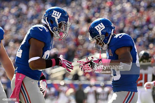 Wide receiver Rueben Randle of the New York Giants celebrates with teammate wide receiver Victor Cruz after catching a three yard pass by quarterback...