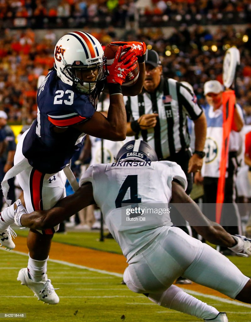 Wide receiver Ryan Davis #23 of the Auburn Tigers dives over cornerback Monquavion Brinson #4 of the Georgia Southern Eagles for a touchdown during the second half of an NCAA college football game at Jordan Hare Stadium on Saturday, September 2, 2017 in Auburn, Alabama.