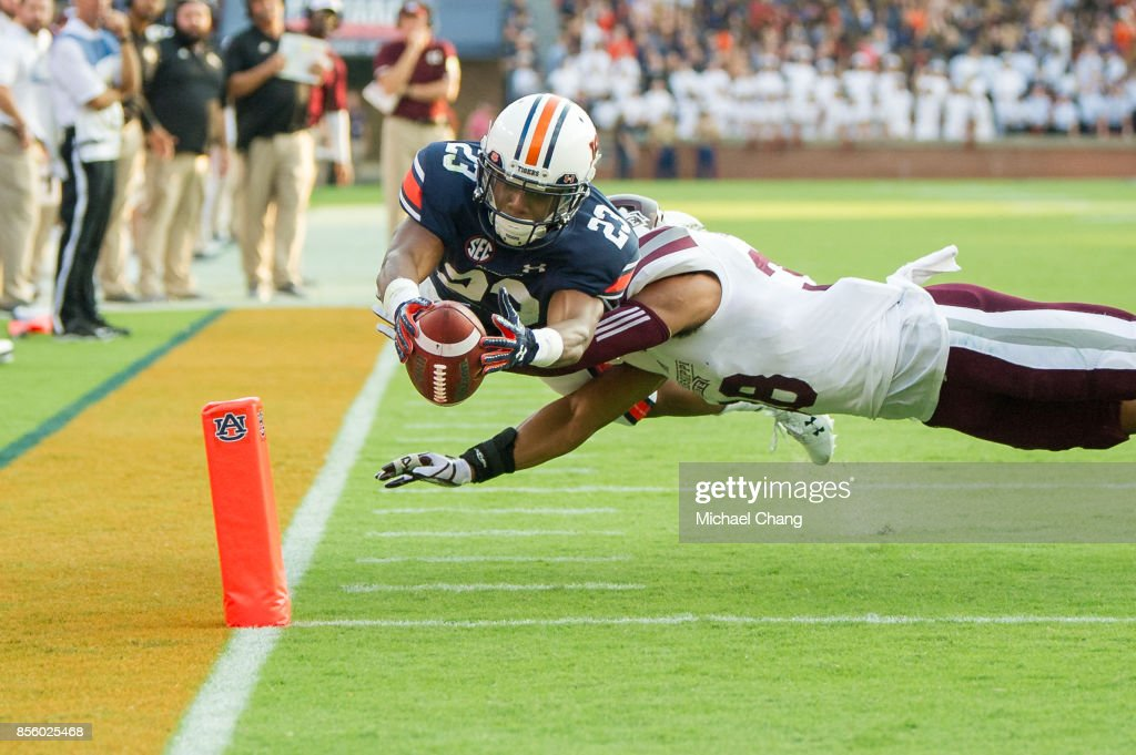 Wide receiver Ryan Davis #23 of the Auburn Tigers leaps into the endzone for a touchdown in front of defensive back Johnathan Abram #38 of the Mississippi State Bulldogs at Jordan-Hare Stadium on September 30, 2017 in Auburn, Alabama.