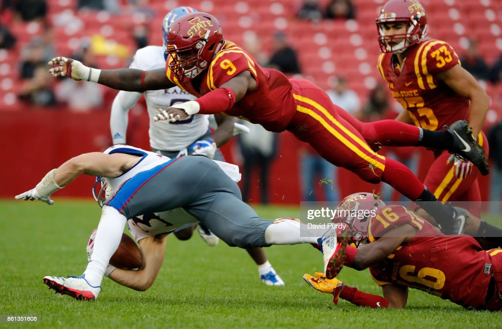 Wide receiver Ryan Schadler #33 of the Kansas Jayhawks is tackled by linebacker Reggan Northrup #9, and defensive back Keontae Jones #16 of the Iowa State Cyclones as he rushed for yards in the second half of play at Jack Trice Stadium on October 14, 2017 in Ames, Iowa. The Iowa State Cyclones won 45-0 over the Kansas Jayhawks.