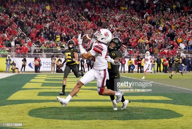 Wide receiver Samson Nacua of the Utah Utes catches a touchdown pass over safety Jevon Holland of the Oregon Ducks during the second half of the...