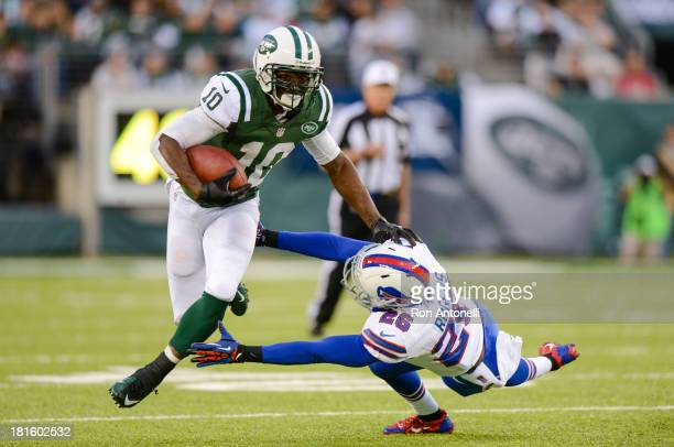 Wide receiver Santonio Holmes of the New York Jets stiff arms defensive back Justin Rogers of the Buffalo Bills as he runs after a catch in the 2nd...