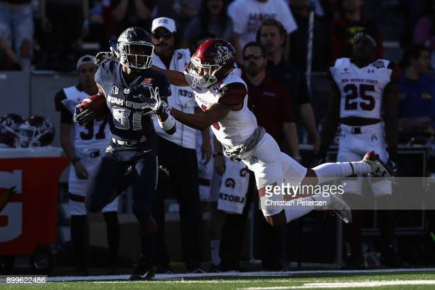 Wide receiver Savon Scarver of the Utah State Aggies returns a kickoff past defensive lineman Stody Bradley of the New Mexico State Aggies for a...