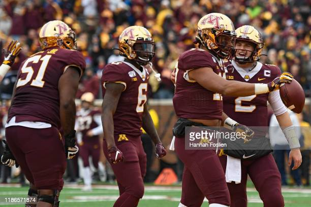 Wide receiver Seth Green of the Minnesota Golden Gophers celebrates his rushing touchdown with teammates against the Penn State Nittany Lions during...