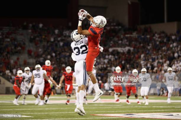 Wide receiver Shawn Poindexter of the Arizona Wildcats makes a leaping catch over defensive back Chris Wilcox of the Brigham Young Cougars during the...