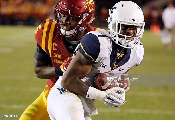 Wide receiver Shelton Gibson of the West Virginia Mountaineers pulls in a reception for a touchdown as defensive back Kamari CottonMoya of the Iowa...