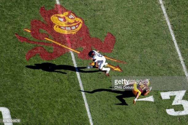 Wide receiver Shun Brown of the Arizona Wildcats slips past defensive back Chad Adams of the Arizona State Sun Devils during the first half of the...