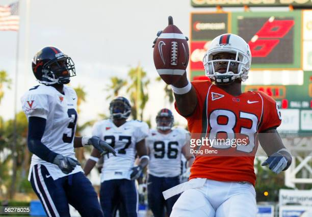 Wide receiver Sinorice Moss of the Miami Hurricanes celebrates his touchdown past defensive back Marcus Hamilton the Virginia Cavaliers at the Orange...