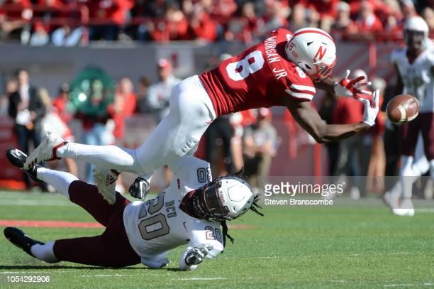 Wide receiver Stanley Morgan Jr #8 of the Nebraska Cornhuskers reaches for a pass as cornerback Trevor Merritt of the Bethune Cookman Wildcats...