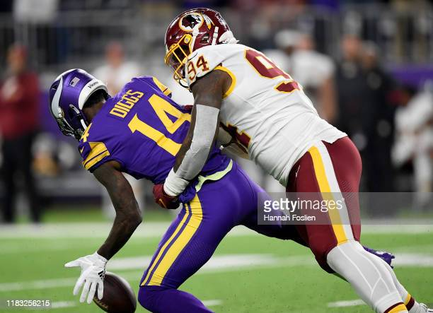 Wide receiver Stefon Diggs of the Minnesota Vikings fumbles the ball as he is hit by Daron Payne of the Washington Redskins during the first quarter...