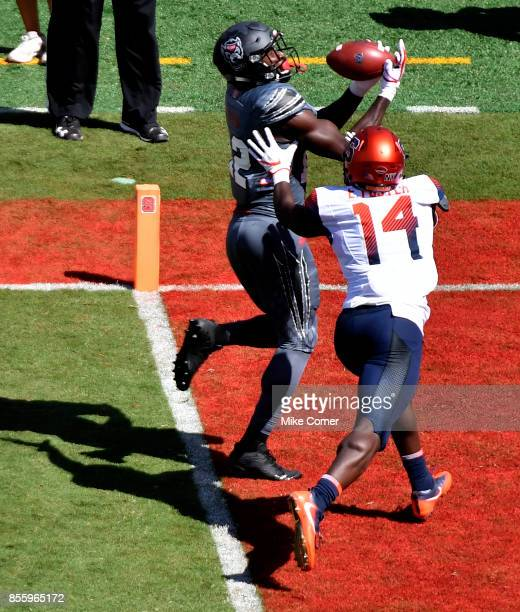 Wide receiver Stephen Louis of the North Carolina State Wolfpack makes a reception for a touchdown over defensive back Evan Foster of the Syracuse...
