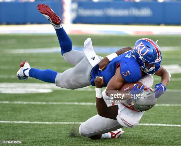 Wide receiver Stephon Robinson of the Kansas Jayhawks is brought down by linebacker Hezekiah White of the Nicholls State Colonels in the first...