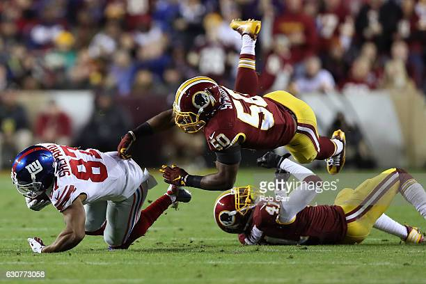 Wide receiver Sterling Shepard of the New York Giants is tackled by outside linebacker Martrell Spaight and free safety Will Blackmon of the...