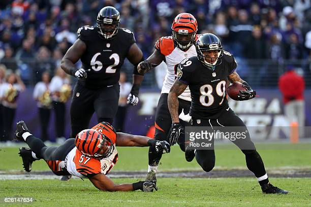Wide receiver Steve Smith of the Baltimore Ravens carries the ball past outside linebacker Vincent Rey of the Cincinnati Bengals in the third quarter...
