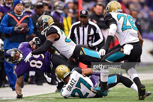 Wide receiver Steve Smith of the Baltimore Ravens is tackled by cornerback Demetrius McCray of the Jacksonville Jaguars and cornerback Dwayne Gratz...