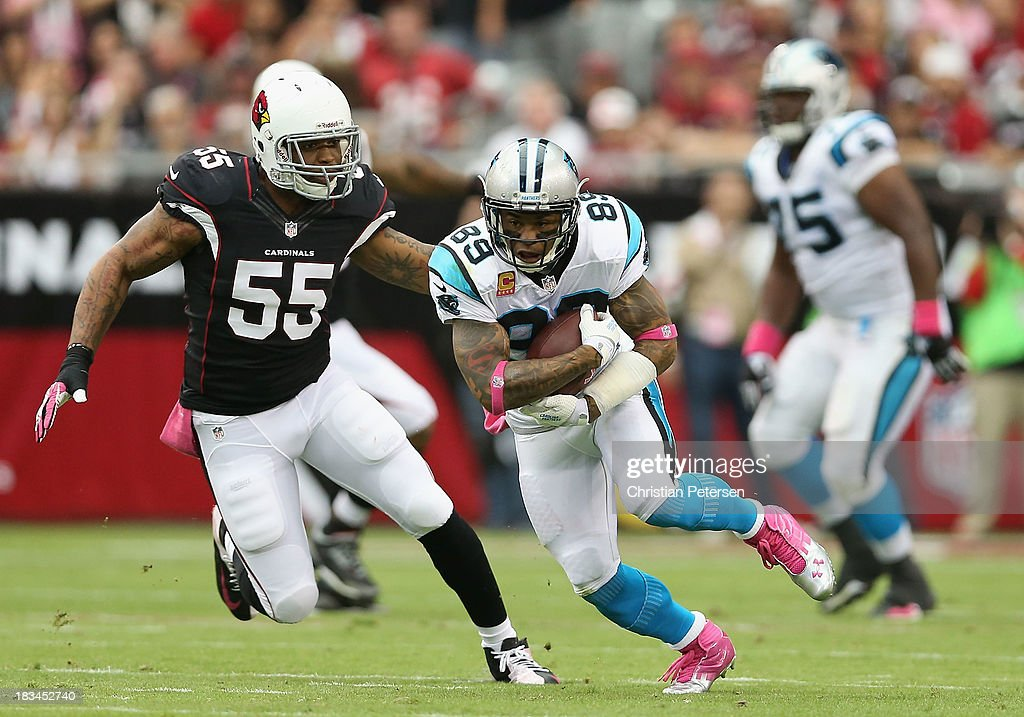 Wide receiver Steve Smith #89 of the Carolina Panthers runs with the football after a reception past defensive end John Abraham #55 of the Arizona Cardinals during the NFL game at the University of Phoenix Stadium on October 6, 2013 in Glendale, Arizona.