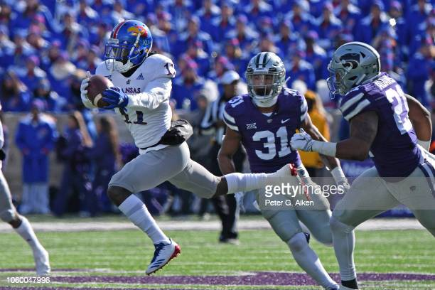 Wide receiver Steven Sims Jr #11 of the Kansas Jayhawks catches a pass and runs for a touchdown against defensive back Kendall Adams and defensive...
