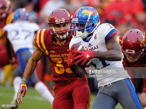 Wide receiver Steven Sims Jr #11 of the Kansas Jayhawks is tackled by defensive back Braxton Lewis of the Iowa State Cyclones as he rushed for yards...