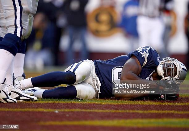 Wide Receiver Terrell Owens of the Dallas Cowboys takes a nap using the ball as a pillow after scoring a touchdown in the third quarter against the...