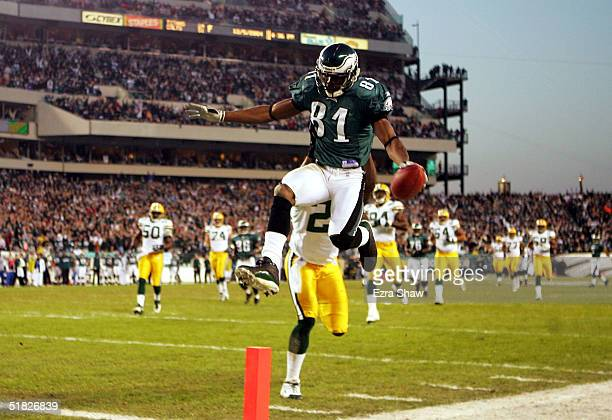 Wide Receiver Terrell Owens of the Philadelphia Eagles leaps into the end zone in front of safety Bhawoh Jue of the Green Bay Packers in the first...
