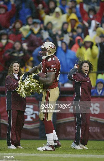 Wide receiver Terrell Owens of the San Francisco 49ers celebrates with a cheerleader's pom poms after scoring a touchdown against the Green Bay...