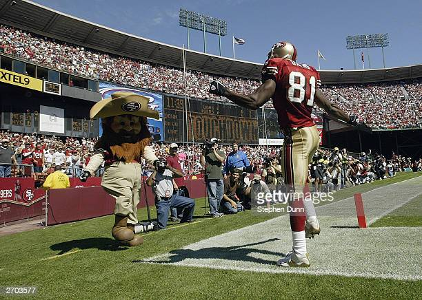 Wide receiver Terrell Owens of the San Francisco 49ers does a dance with 'Sourdough Sam' to celebrate his touchdown catch against the Detroit Lions...