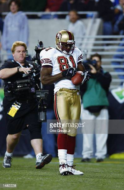 Wide receiver Terrell Owens of the San Francisco 49ers pulls a pen out of his sock and signs the football after scoring a touchdown against the...