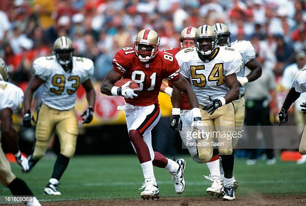 Wide Receiver Terrell Owens of the San Francisco 49ers runs with the ball after a reception pursued by Winfred Tubbs of the New Orleans Saints during...