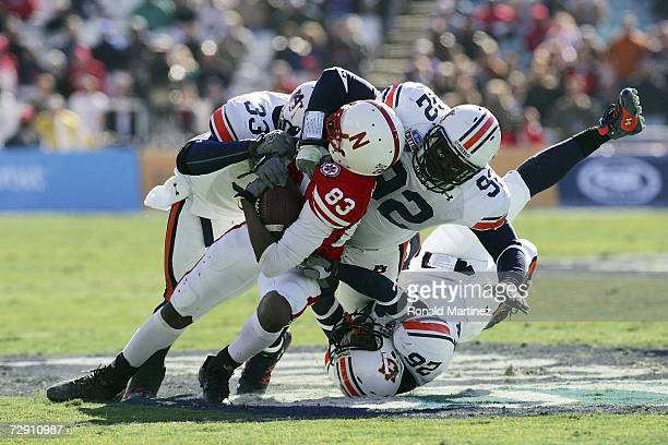 Wide receiver Terrence Nunn of the Nebraska Cornhuskers is tackled by Eric Brock Christopher Browder and Steve Gandy of the Auburn Tigers during the...