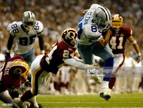 Wide receiver Terry Glenn of the Dallas Cowboys jumps over the tackle by Champ Bailey of the Washington Redskins for a touchdown on November 2 2003...