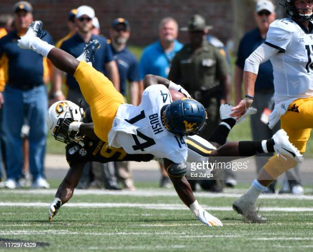 Wide receiver Tevin Bush of the West Virginia Mountaineers is tackled by safety Tyree Gillespie of the Missouri Tigers in the second half at Faurot...