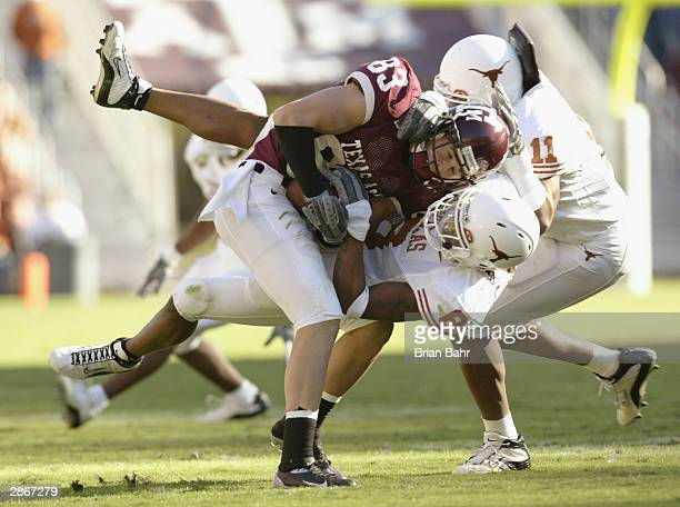 Wide receiver Tim Van Zant of the Texas AM University Aggies is tackled by cornerback Cedric Griffin and linebacker Derrick Johnson of the University...