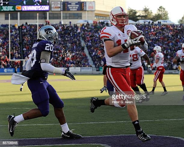 Wide receiver Todd Peterson of the Nebraska Cornhuskers catches a 5yard touchdown pass in front of defensive back Courtney Herndon of the Kansas...