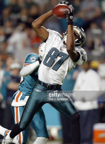 Wide receiver Todd Pinkston of the Philadelphia Eagles makes a catch before being stopped by cornerback Sam Madison of the Miami Dolphins December 15...