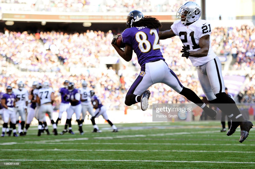 Wide receiver Torrey Smith #82 of the Baltimore Ravens catches a pass for a touchdown past cornerback Ron Bartell #21 of the Oakland Raiders in the third quarter at M&T Bank Stadium on November 11, 2012 in Baltimore, Maryland. The Baltimore Ravens won, 55-20.