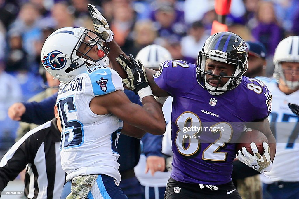 Wide receiver Torrey Smith #82 of the Baltimore Ravens is shoved out of bounds by cornerback Blidi Wreh-Wilson #25 of the Tennessee Titans in the third quarter of a game at M&T Bank Stadium on November 9, 2014 in Baltimore, Maryland.